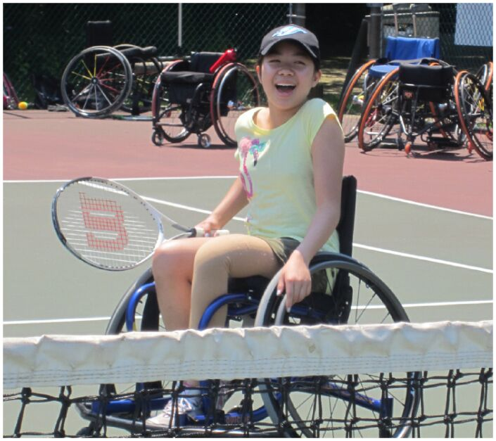 Young girl enjoying wheelchair tennis