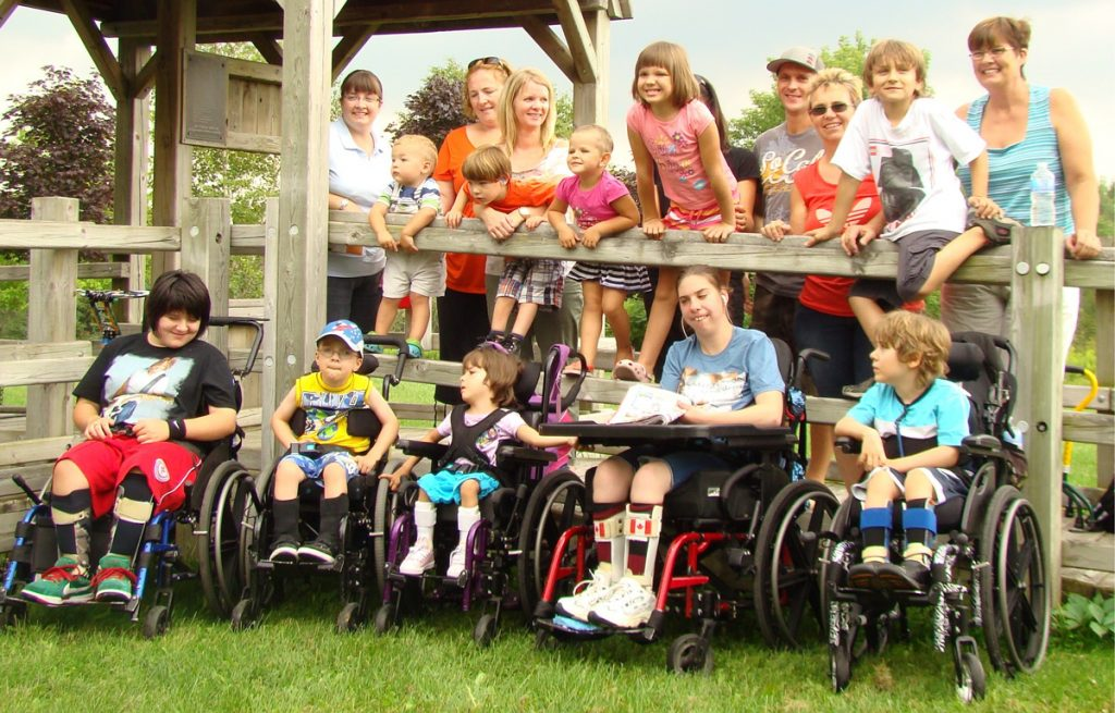 many children with disabilities in wheelchairs with able-bodied children and parents leaning on a wooden railing behind them