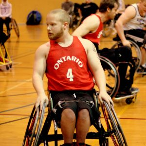 A front-facing photo of athlete Eric Voss in his basketball wheelchair wearing a red Ontario jersey #4