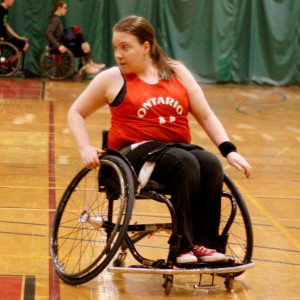 a girl wearing a red Ontario jersey in a basketball wheelchair pivoting to the left during a game