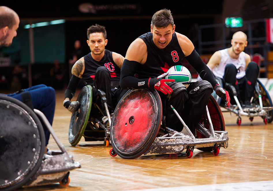 a wheelchair rugby player pushes his rugby chair while protecting the ball