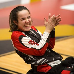 A young girl athlete smiles and claps her hands during a wheelchair basketball game