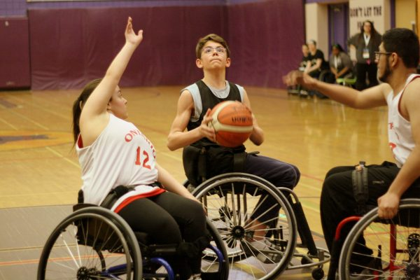A young boy in a wheelchair prepares to shoot a basketball while two athletes, a boy and a girl, raise their hands to defend the shot