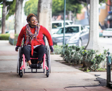 A Black woman wheels along the sidewalk in a pink wheelchair. She is smiling and wearing a red jacket, black pants, black gloves, and a multi-coloured knit scarf